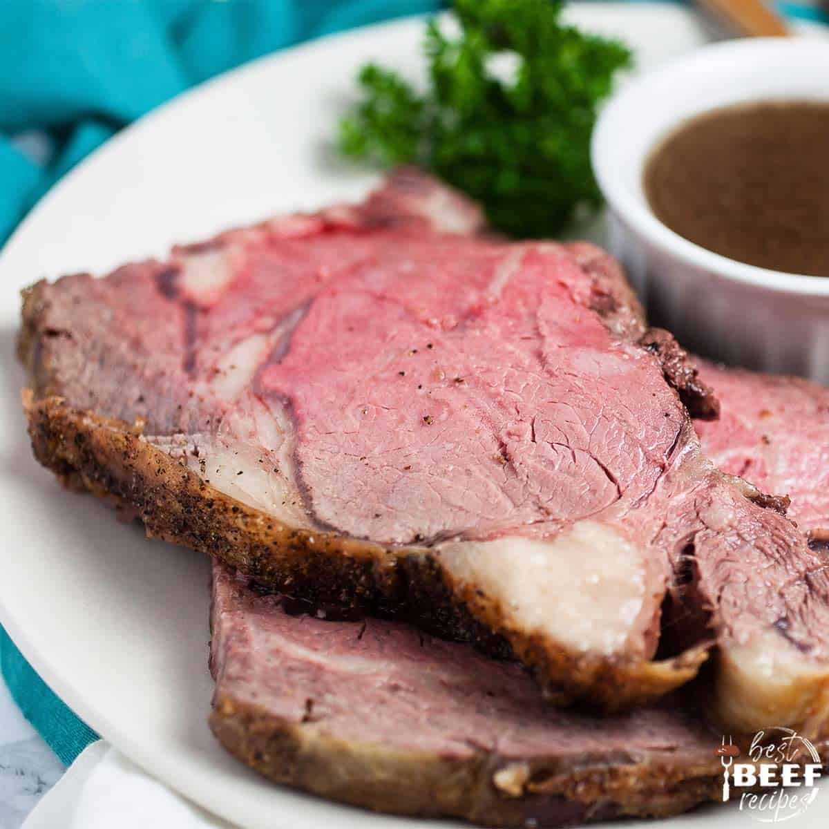 Two slices of boneless prime rib roast on a white plate