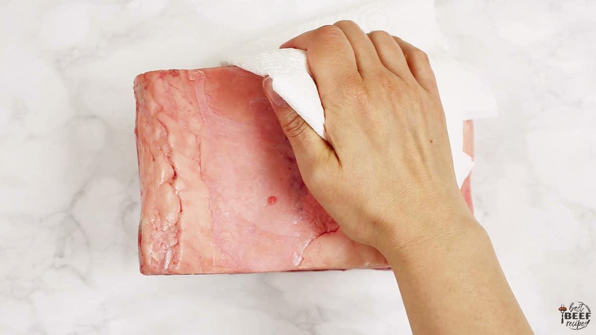 Patting a boneless rib roast dry with a paper towel