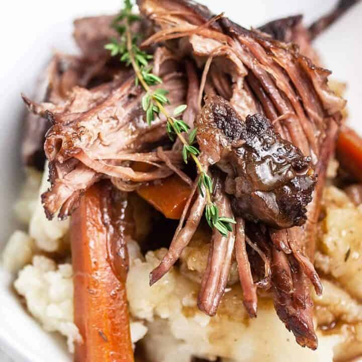 Close up of Dutch Oven Pot Roast with a sprig of rosemary on top and mashed potatoes underneath