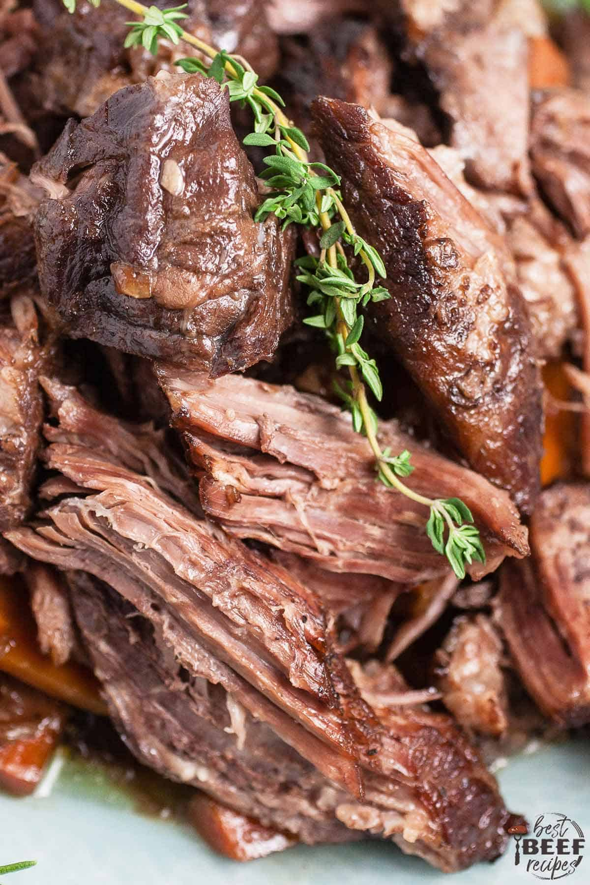 Close up of pot roast beef on a plate with a sprig of rosemary