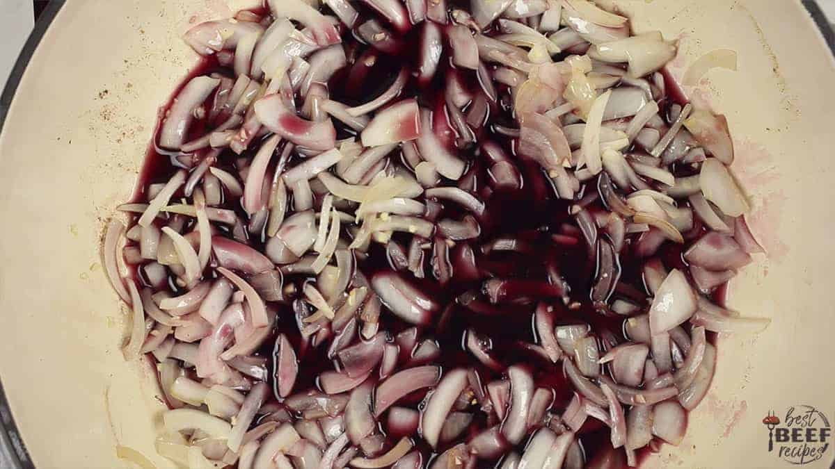 Red wine added to onions and garlic in the dutch oven