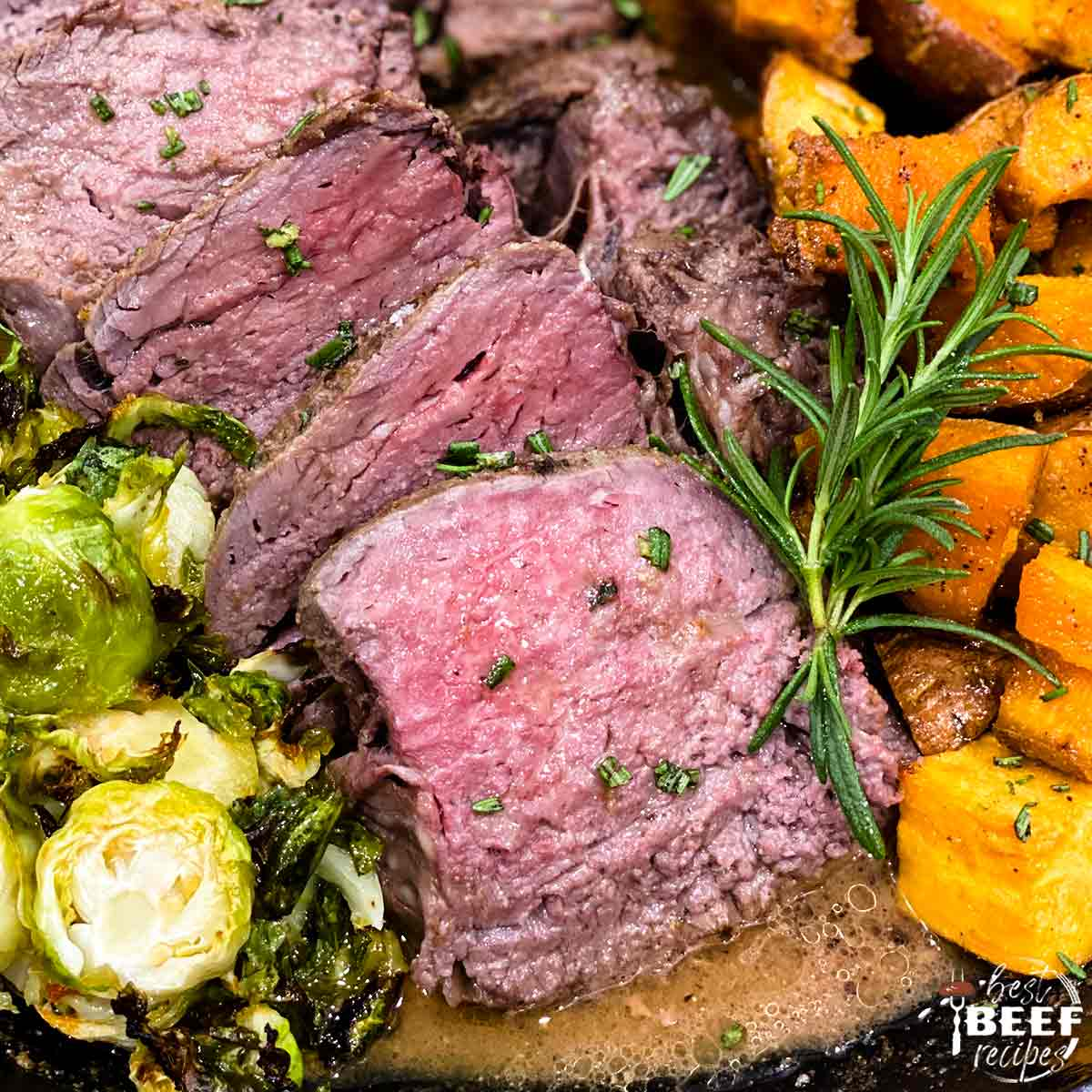 Sous vide tenderloin sliced in a skillet with sweet potatoes and brussels sprouts