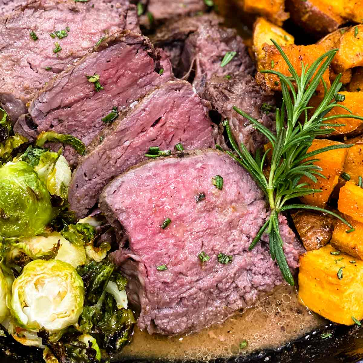 Sous vide tenderloin sliced in a skillet with sweet potatoes, garlic butter, and brussels sprouts