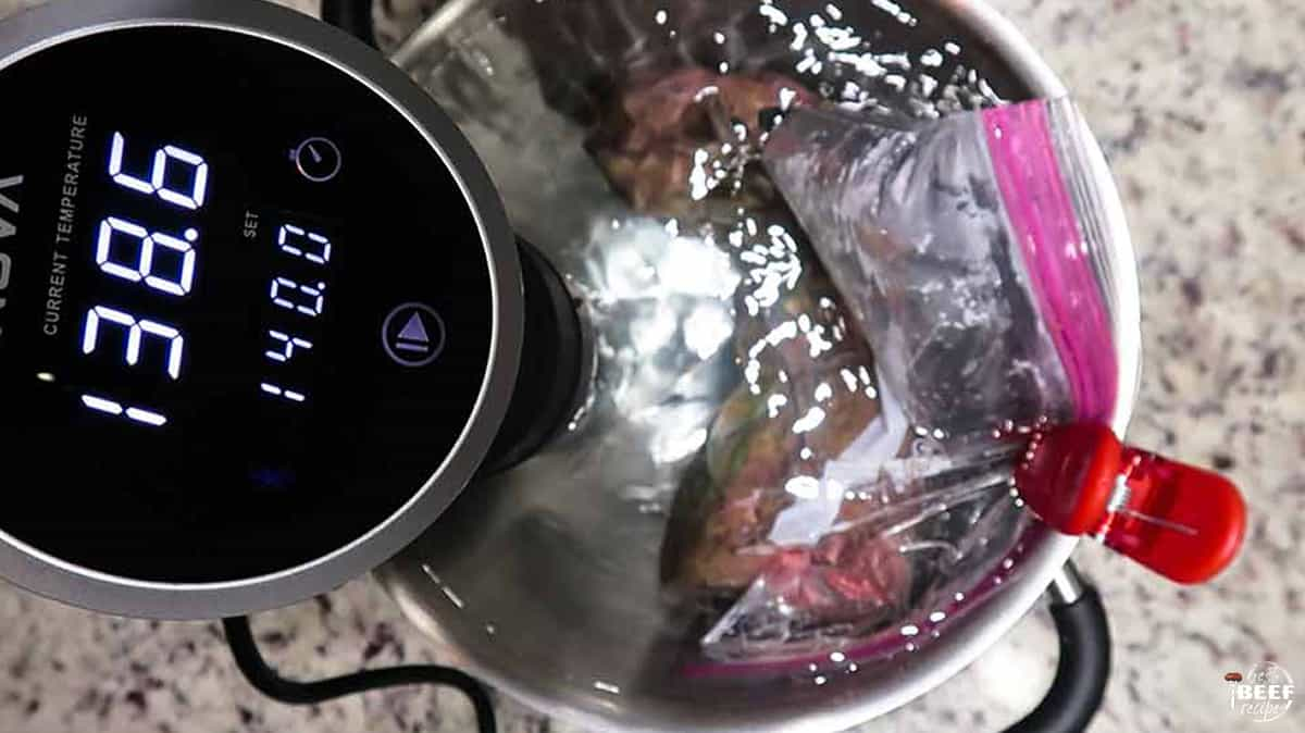 Sous vide cooker attached to a pot with the bag of tenderloin clipped to the side