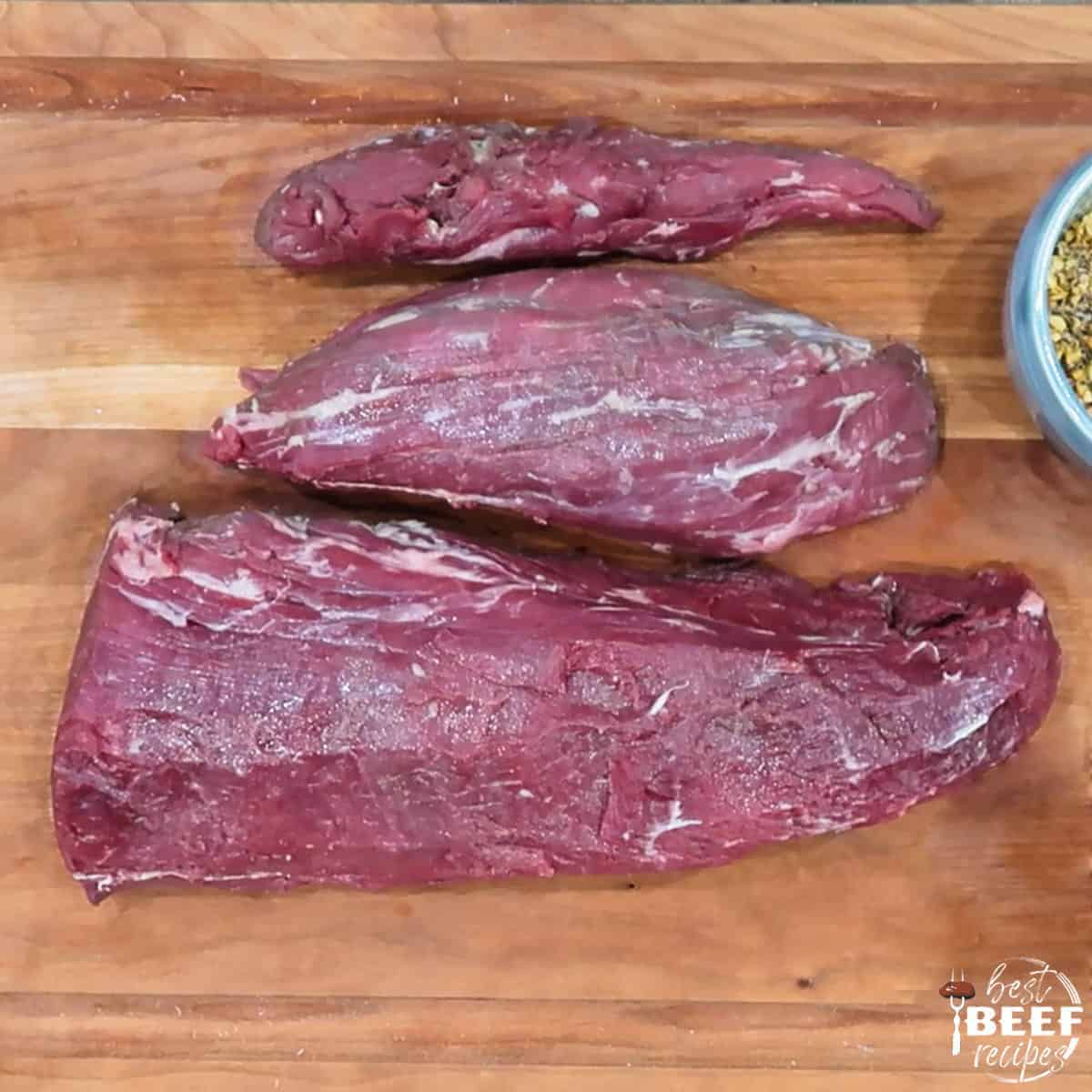 Trimmed beef tenderloin on a cutting board