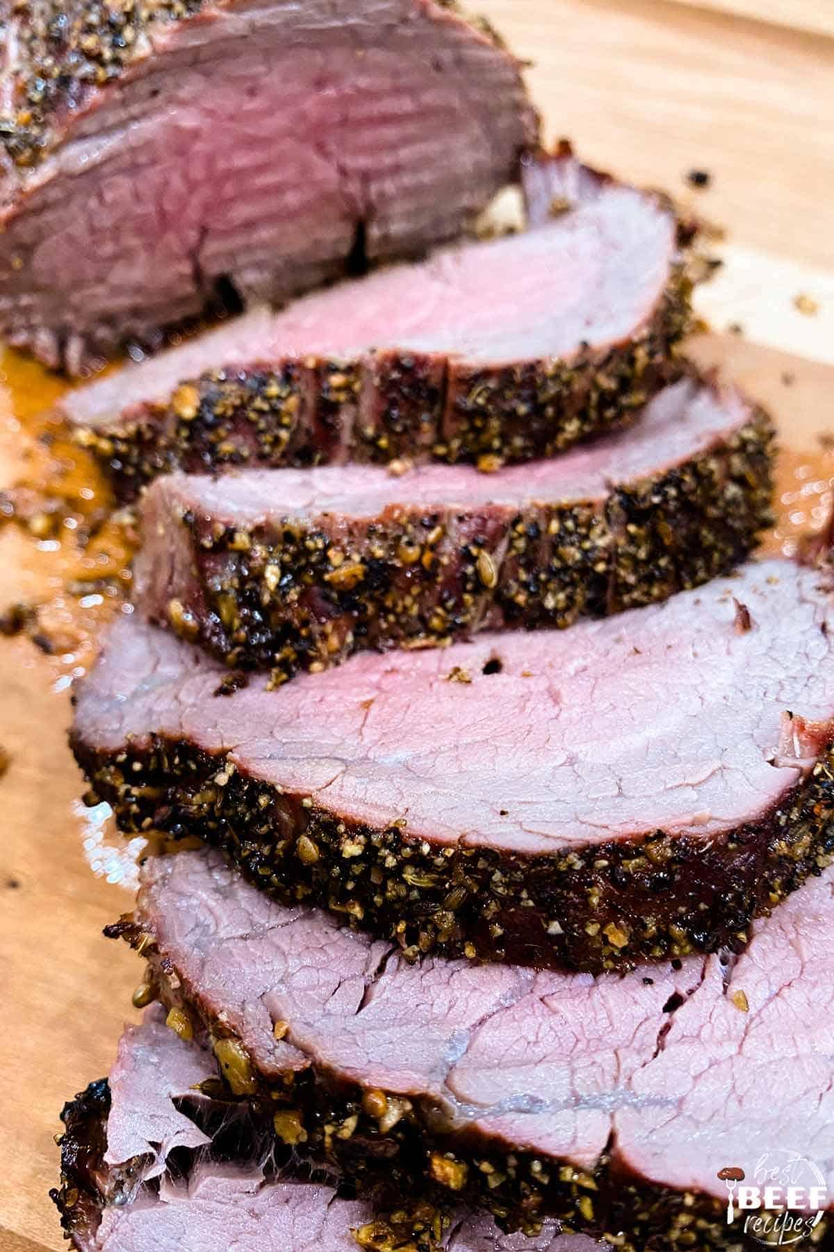 Sliced beef tenderloin on a cutting board up close