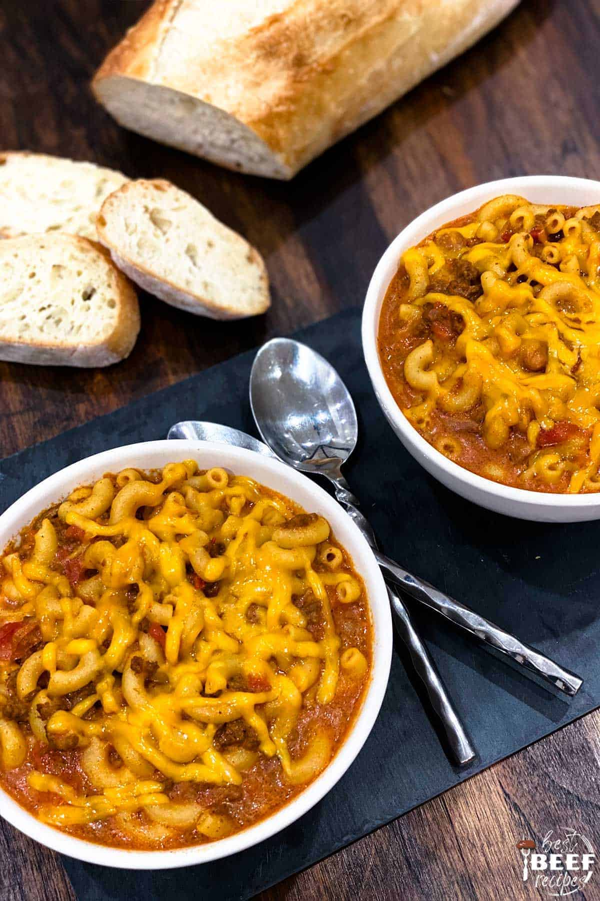 Instant pot chili mac in two white bowls with two spoons and slices of bread