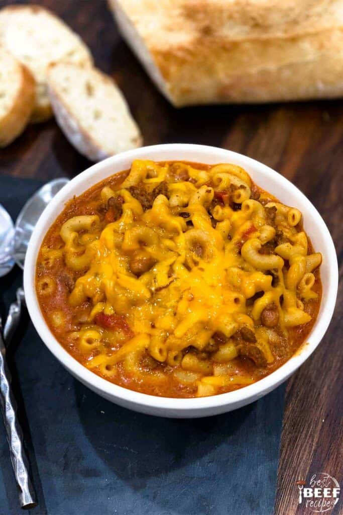 A single bowl of instant pot chili mac next to two spoons