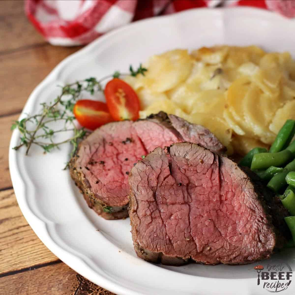 Two slices of whole beef tenderloin next to potatoes and green beans on a plate