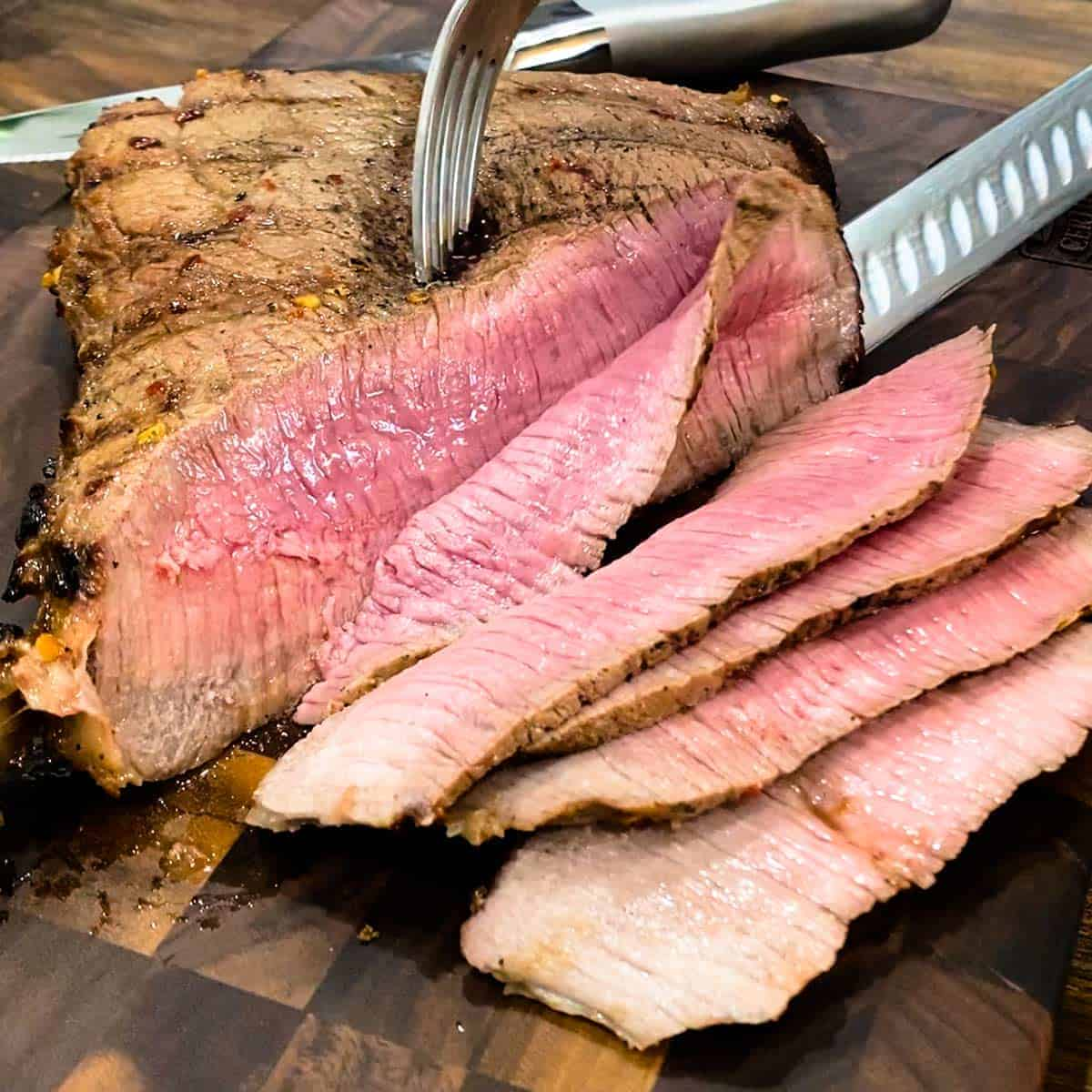 Slicing a grilled london broil on a cutting board with a fork and knife