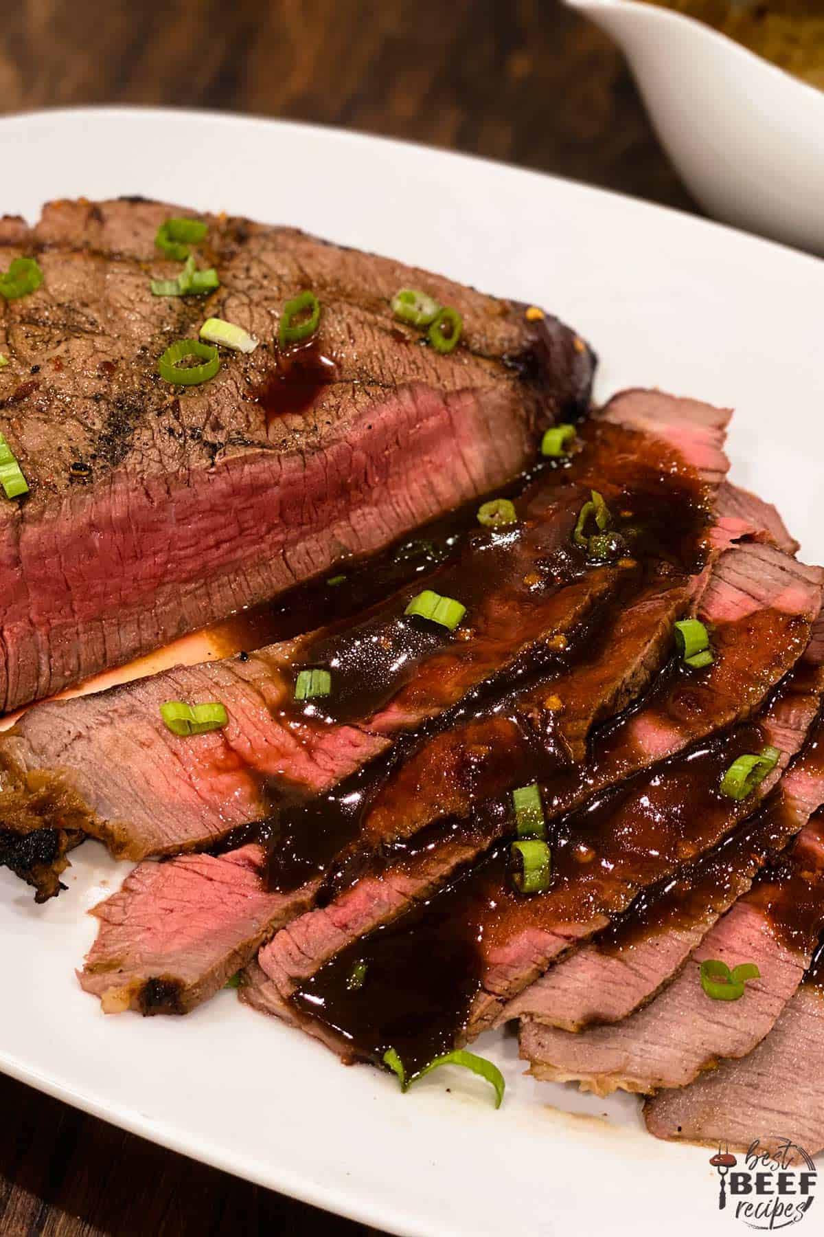 Slices of grilled london broil topped with sauce and green onions on a white platter