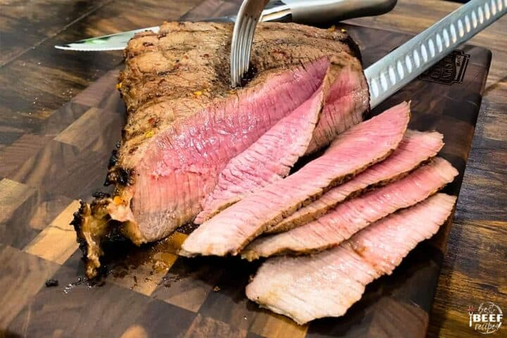 Slicing london broil with a fork and knife on a cutting board