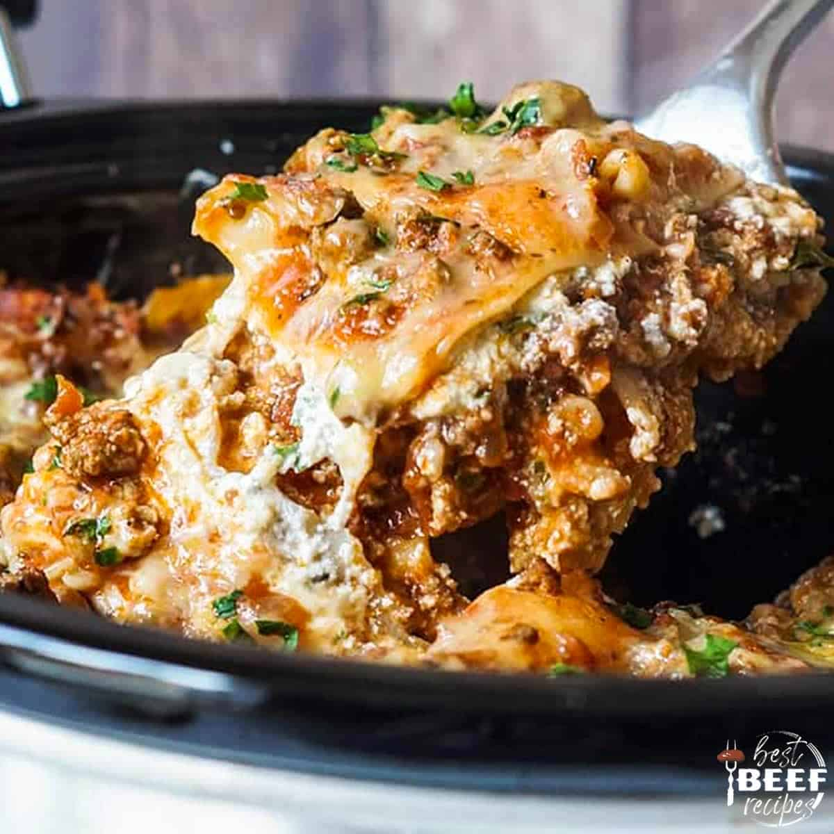Slow cooker lasagna in the crock pot with a fork lifting some out
