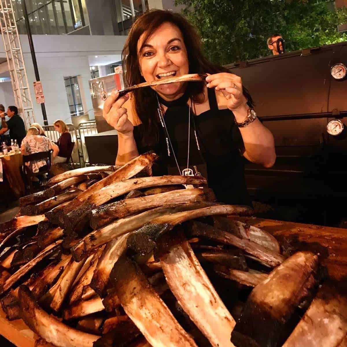 Isabel smiling with a stack of ribs