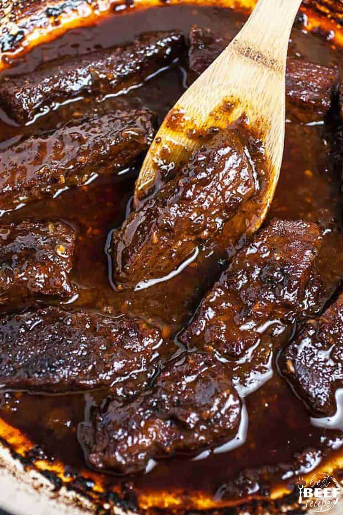 Cooked Korean beef short ribs with a wooden spoon in a Dutch oven