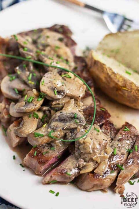 Steak diane on a white plate with potatoes