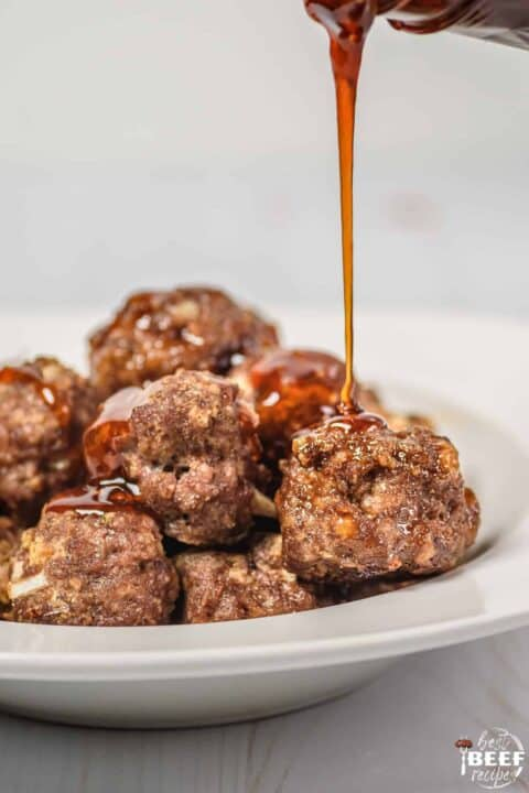 Drizzling honey sriracha sauce on meatballs