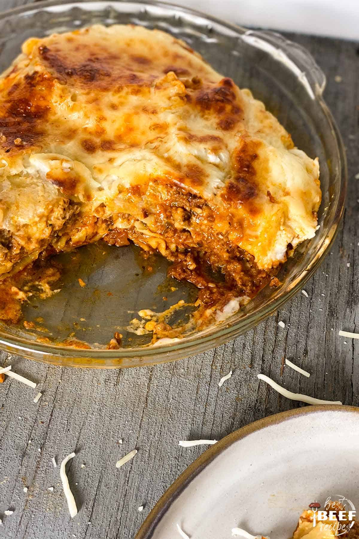 Beef lasagna in a glass dish with a slice missing