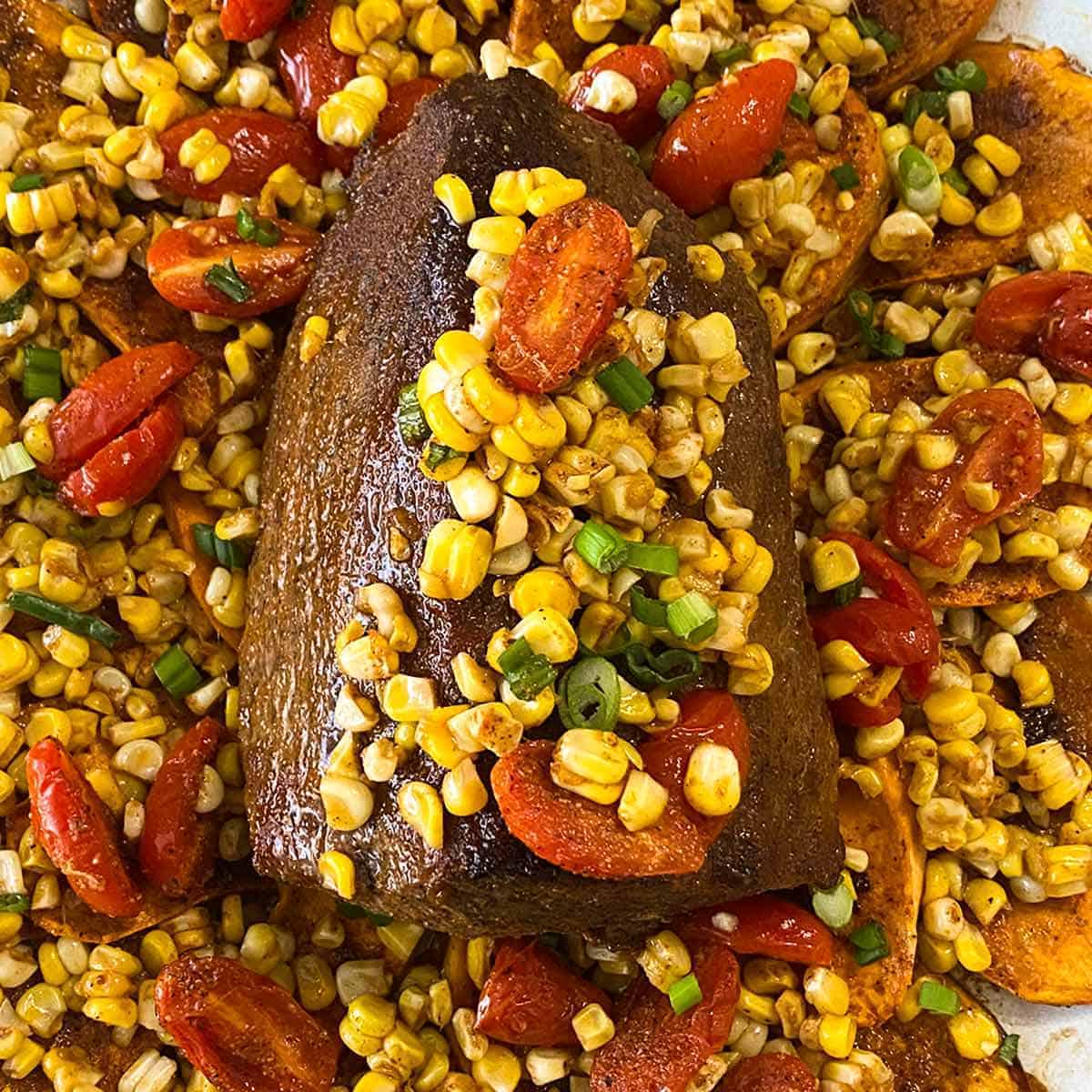 Eye of round roast on a bed of sweet potatoes with corn and tomatoes