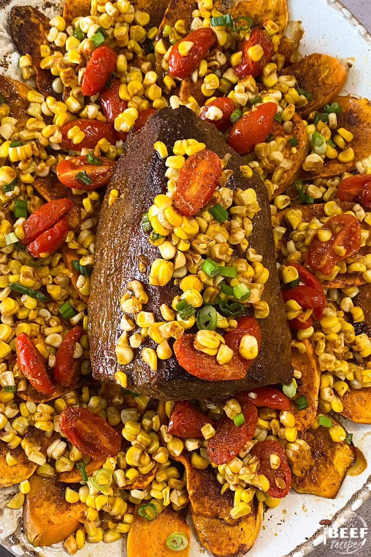 Eye round roast on a bed of sweet potatoes with corn and tomatoes