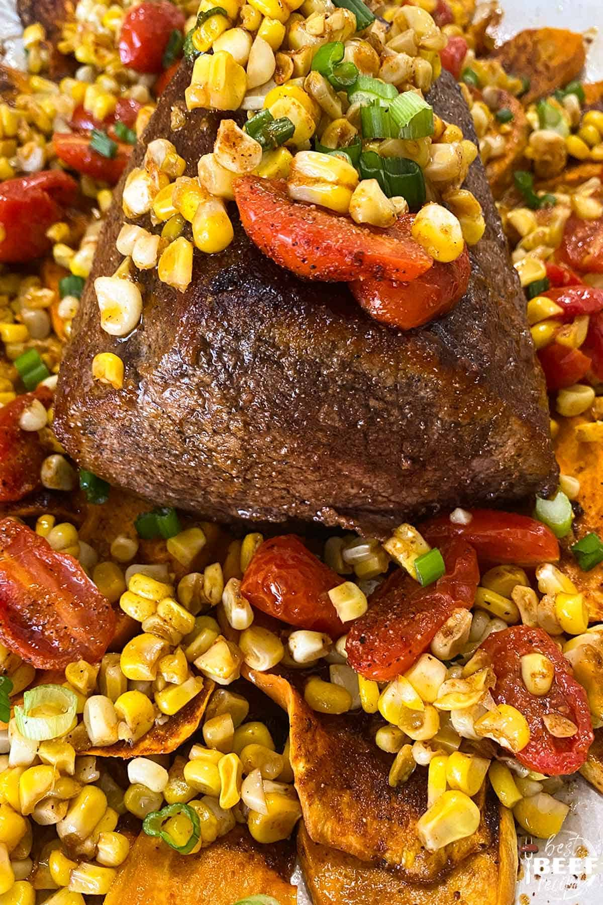 Whole eye of round roast on corn and tomatoes