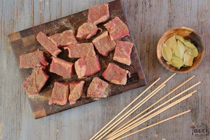 Cubes of seasoned beef on a cutting board with skewers to the side
