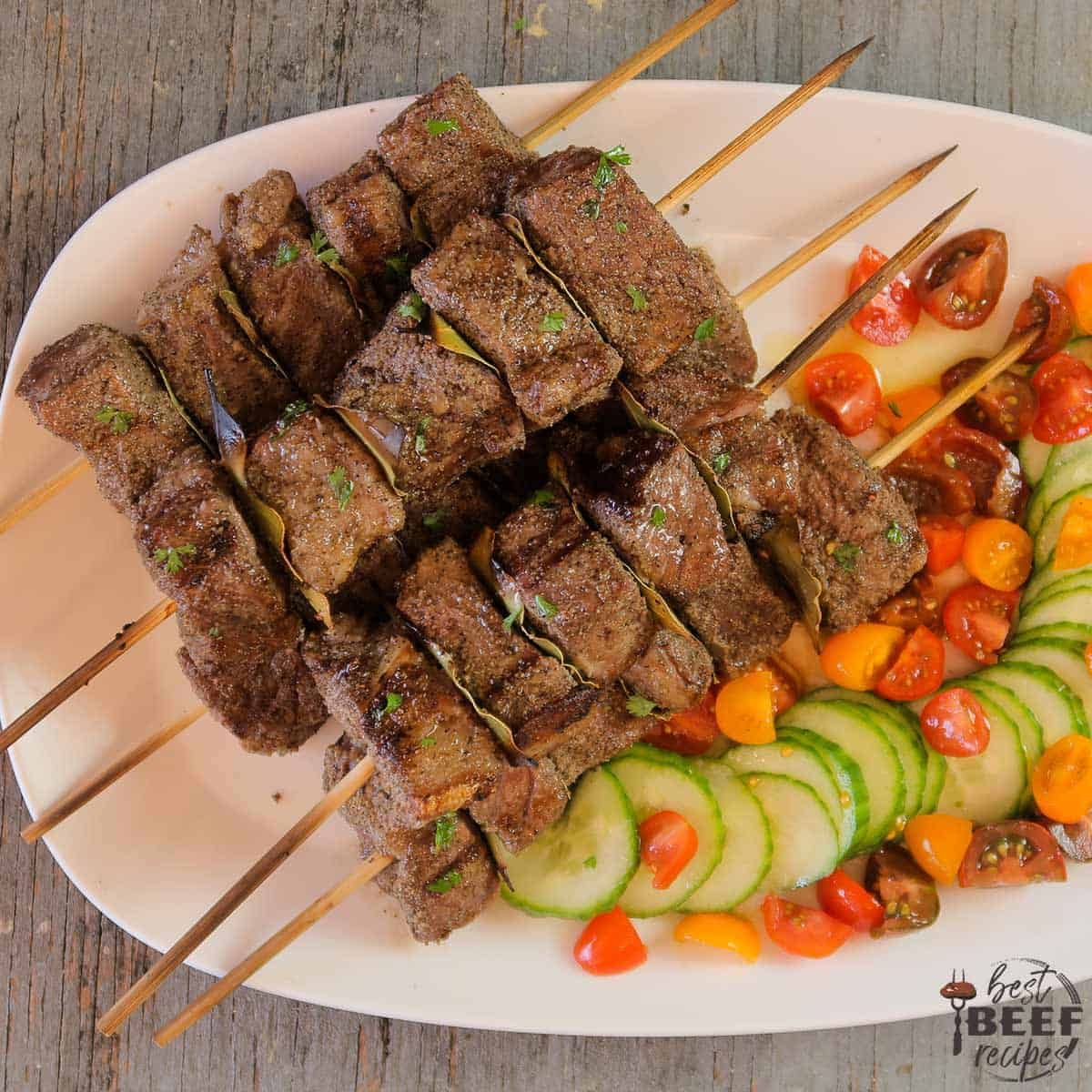 Beef kabobs with a tomato cucumber salad on a white platter