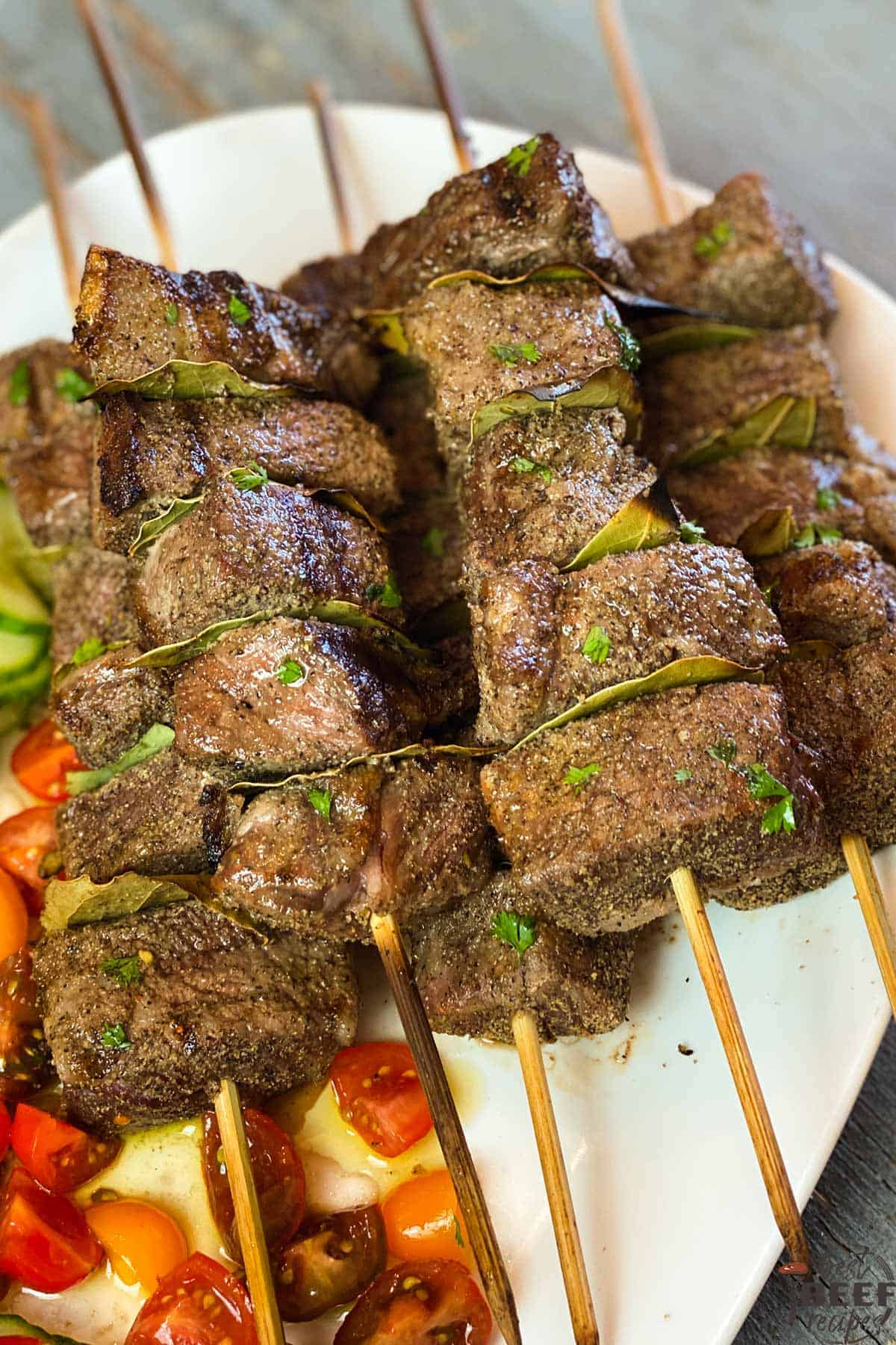 Grilled beef kabobs on skewers on a white plate