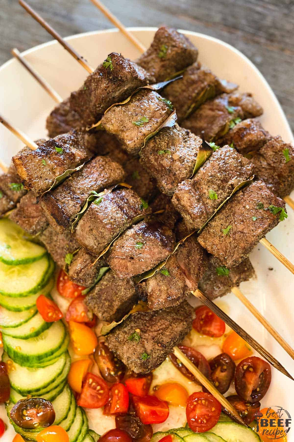 Beef kabobs on a white platter with cucumber and tomatoes