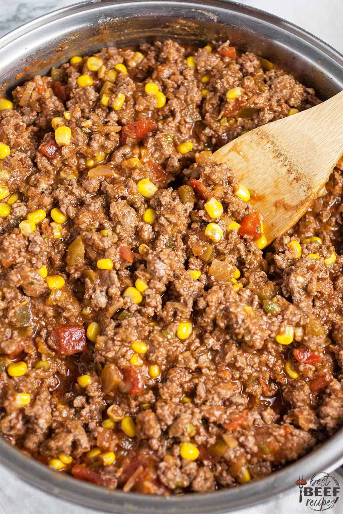 Stirring ground beef with tomatoes and corn