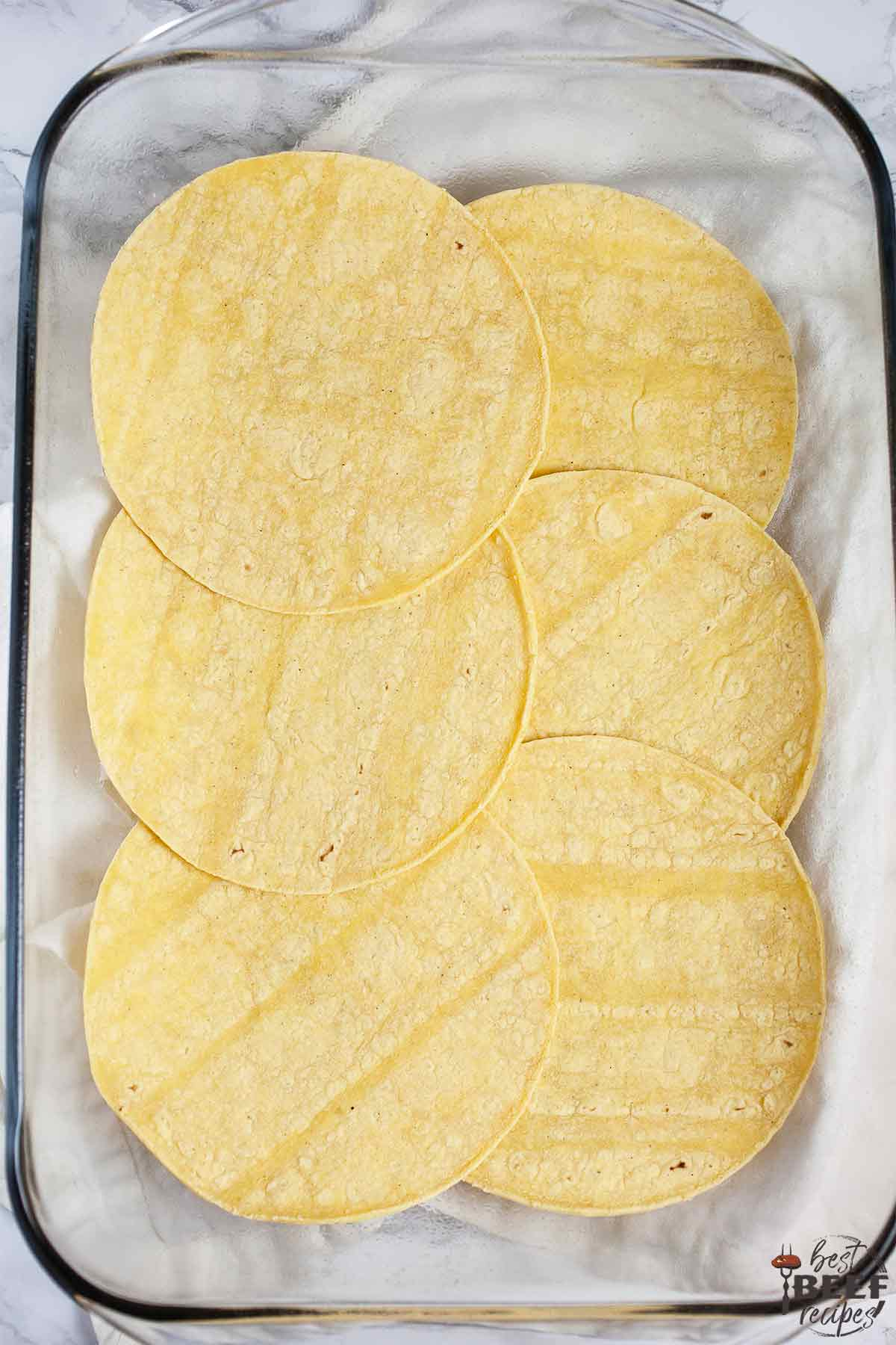 Layering corn tortillas in a glass dish