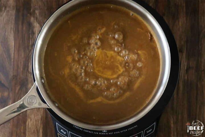 Poutine gravy simmering in skillet