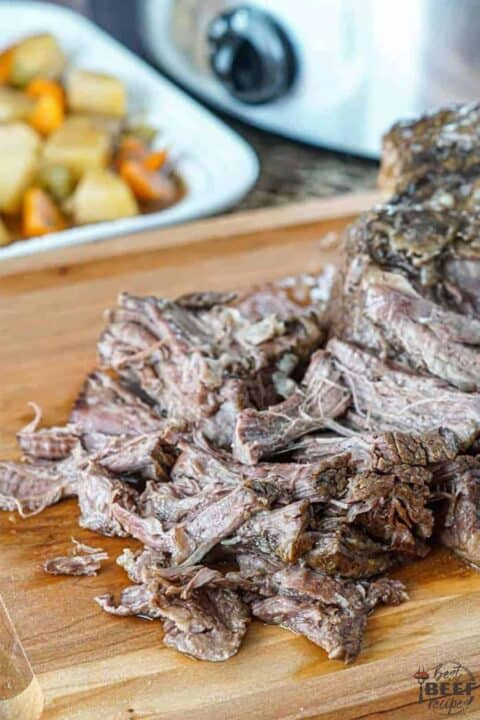 Slow cooker roast beef shredded on cutting board