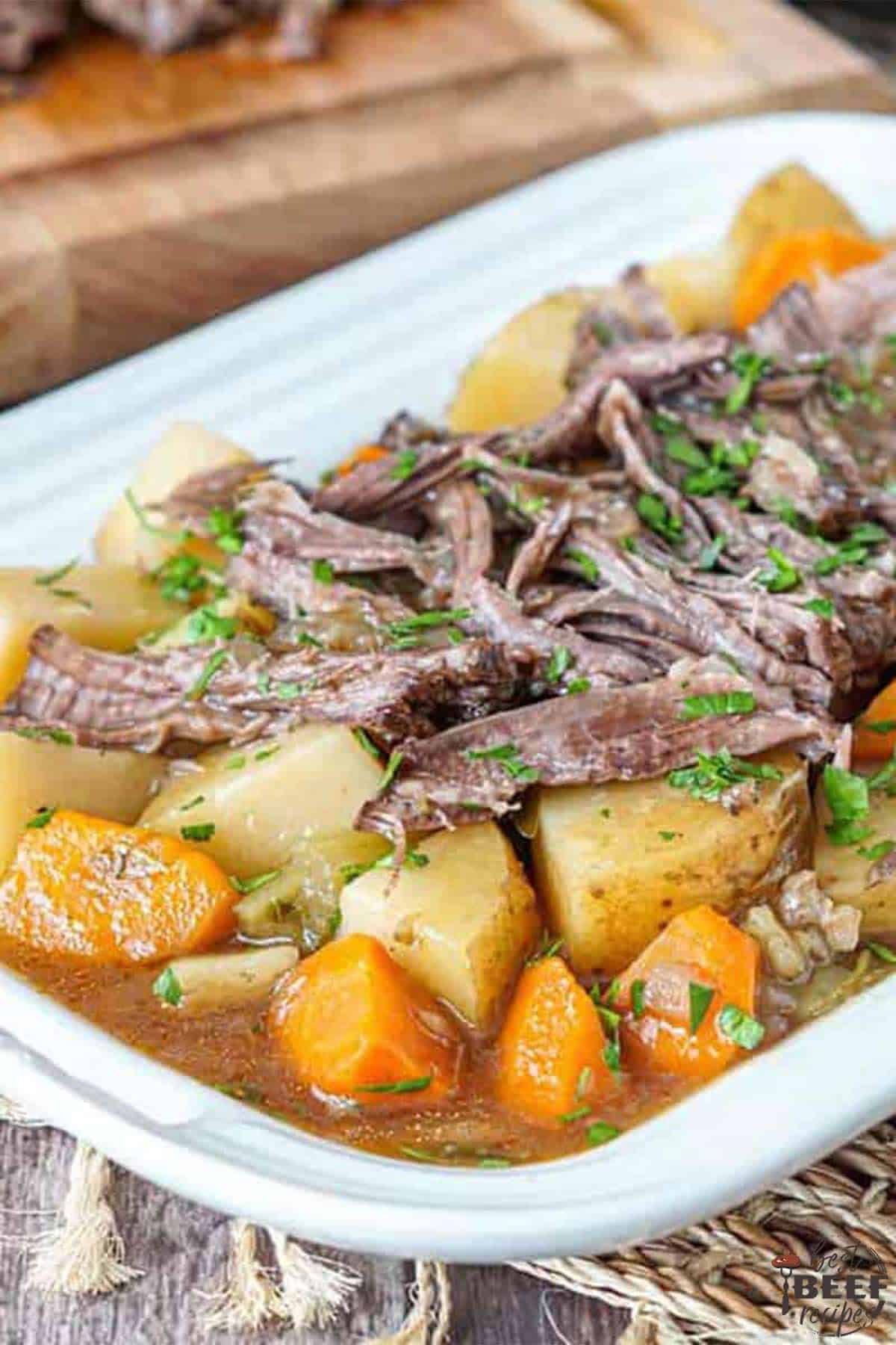 Shredded slow cooker roast beef with potatoes and carrots on a white dish