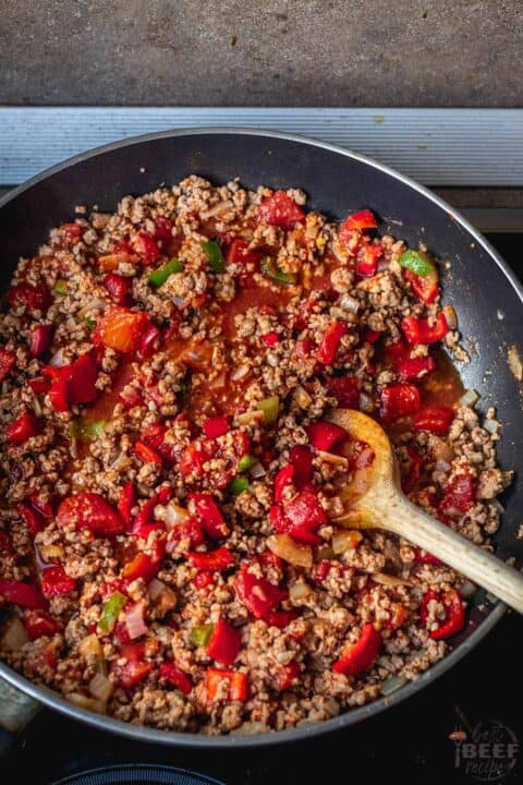 Adding seasoning and tomatoes to ground beef in skillet