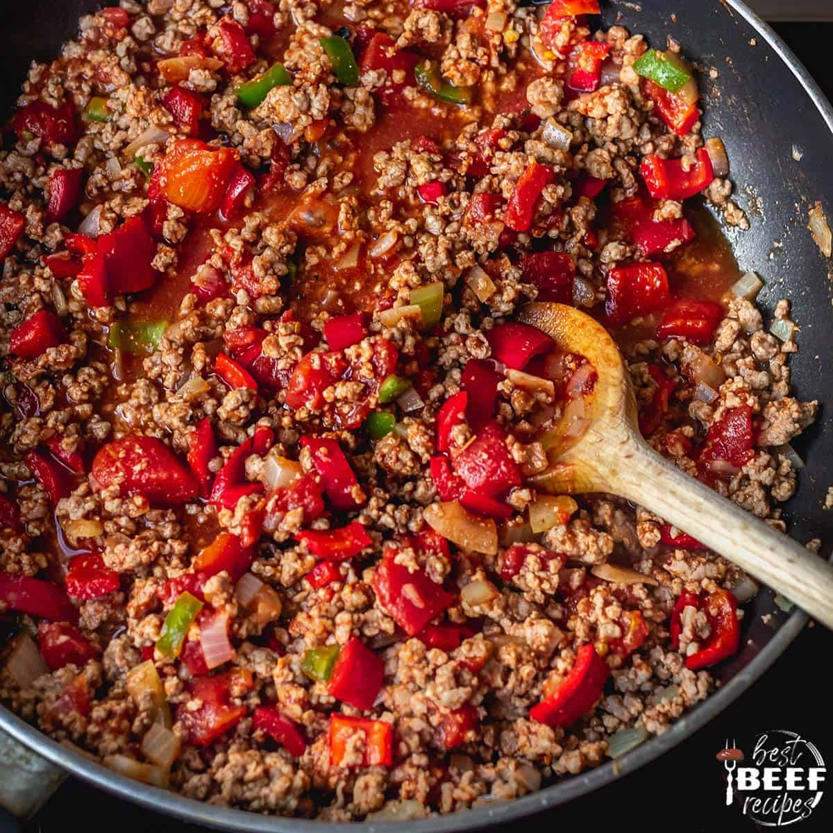 Ground beef cooking in a skillet with seasonings and peppers