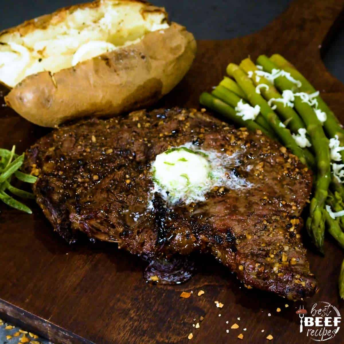 Grilled rib eye steak on a cutting board with asparagus and a baked potato