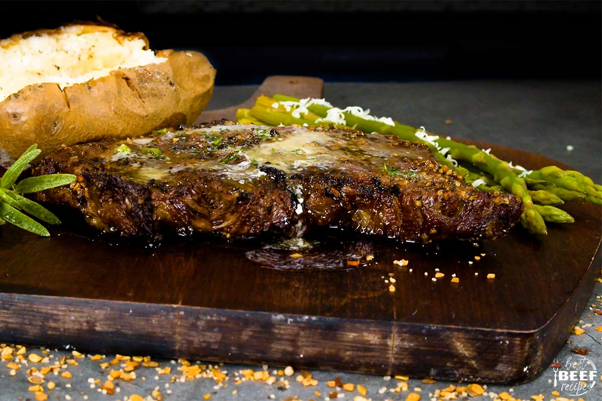 Close up of garlic butter dripping off of grilled rib eye steak