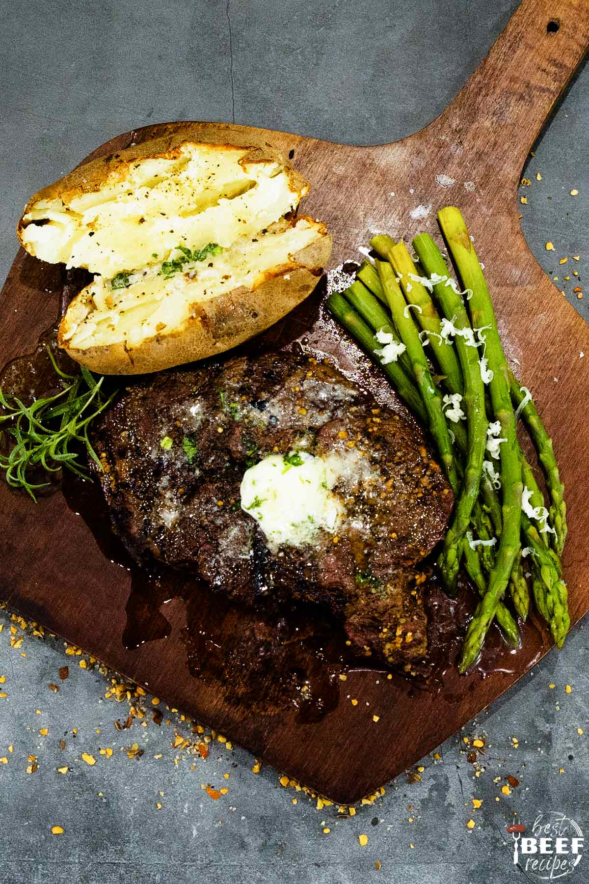 Overhead photo of rib eye steak with garlic butter next to asparagus and baked potato
