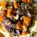 Beef short ribs over mashed potatoes on a plate