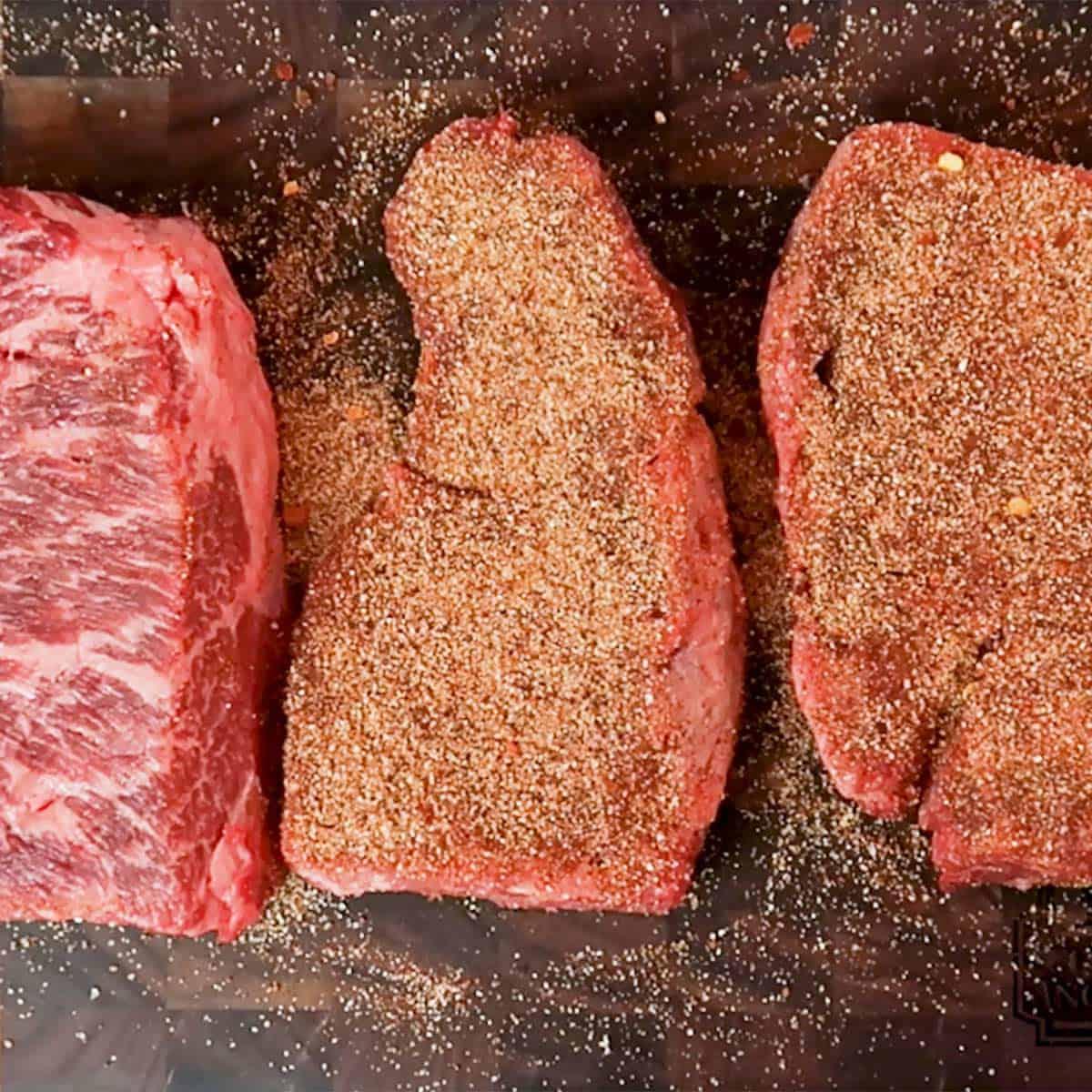 Three seasoned steaks on a cutting board