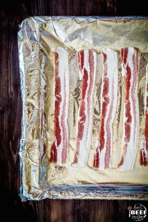 Raw bacon on a foil-lined baking sheet