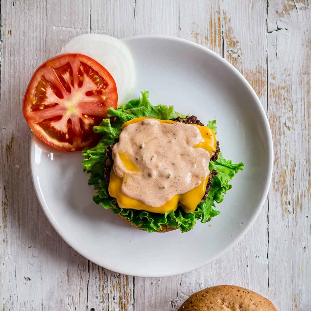 Burger sauce on top of a burger on a plate