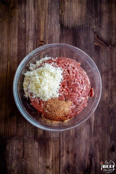 Parmesan, ground beef, and seasoning in a bowl