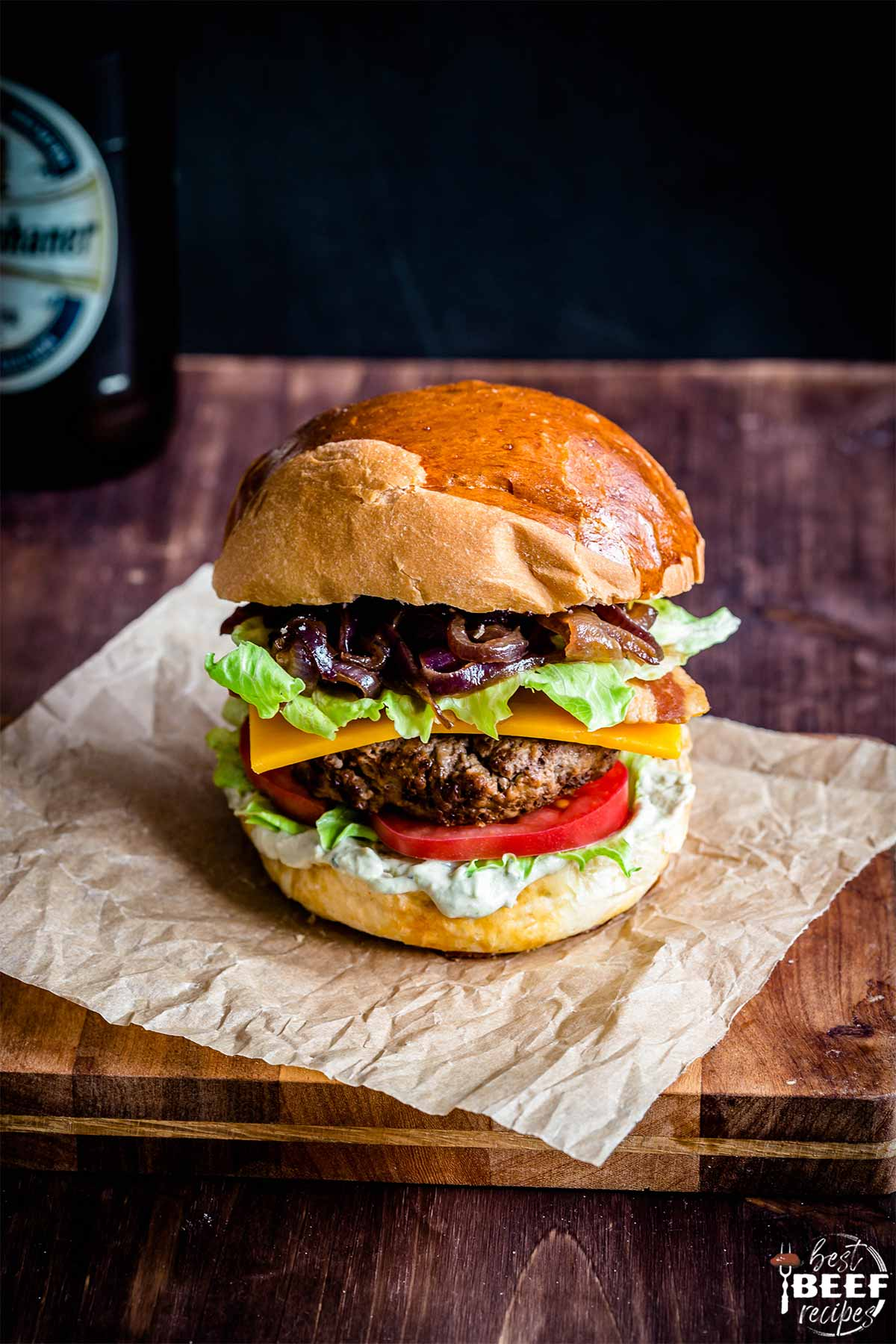 Close up of a loaded burger on a sheet of parchment paper