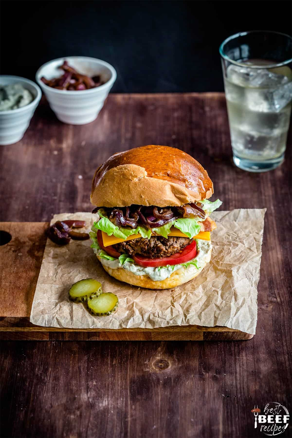 Loaded burger on a sheet of parchment paper with a drink in a glass and toppings in cups