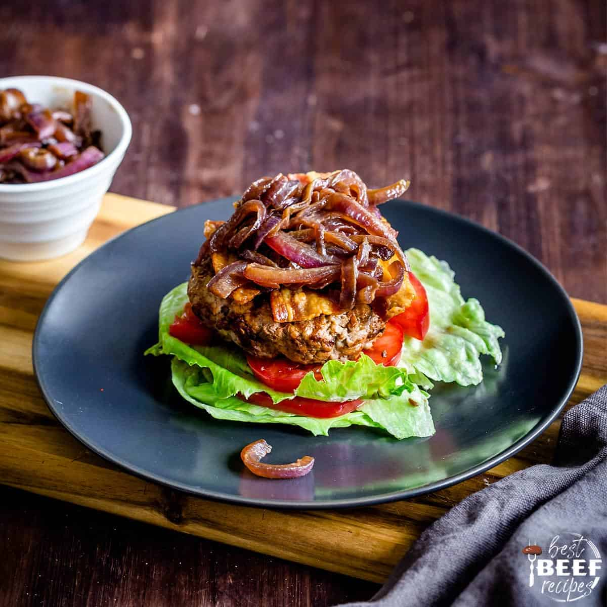 Keto burgers topped with caramelized onions on a bed of tomatoes and lettuce