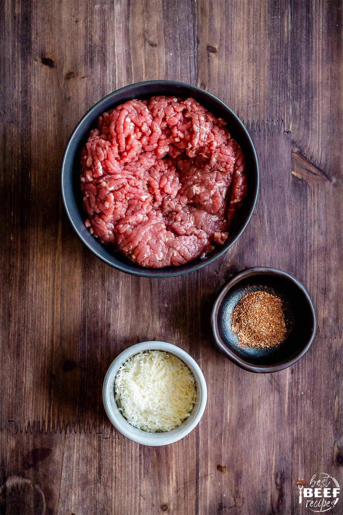 Ground beef, parmesan, and seasoning in bowls