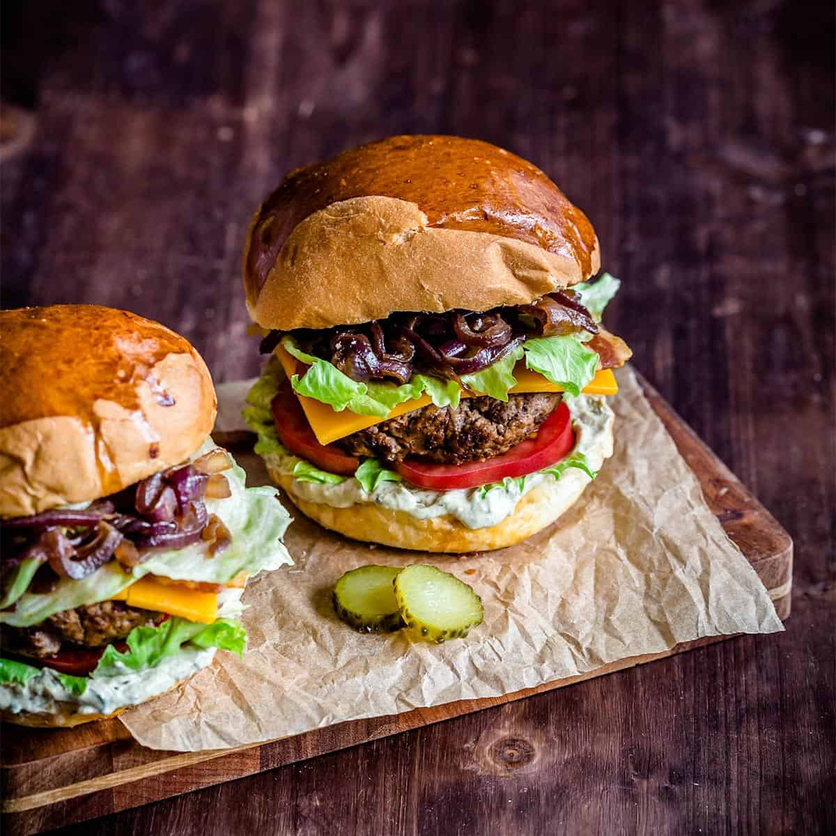 Two loaded burgers on a piece of parchment paper