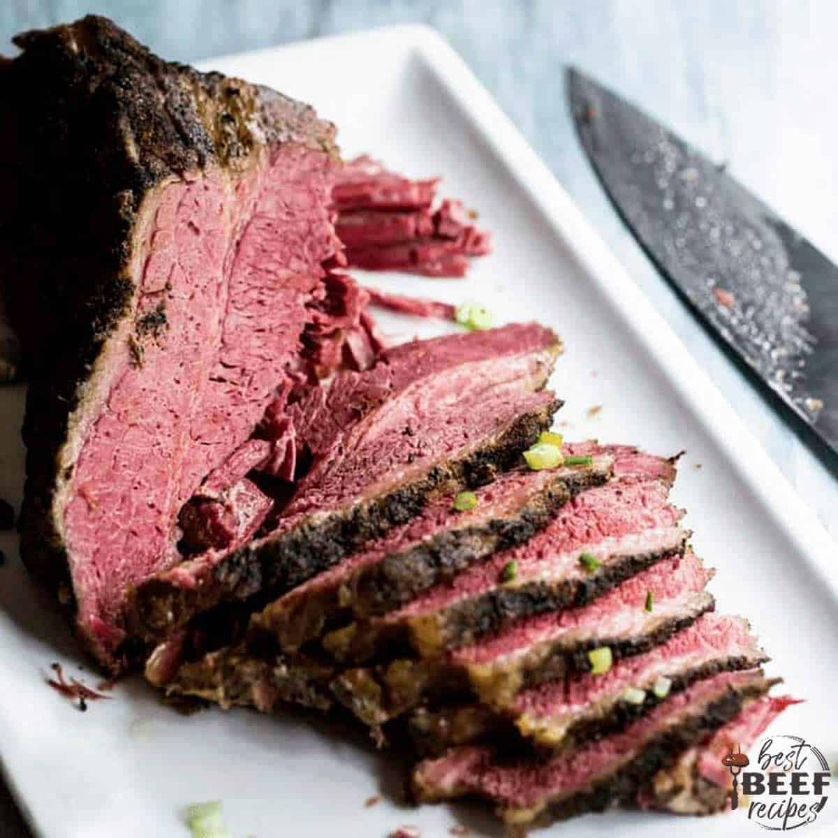 Slow cooker beef brisket sliced on a white platter